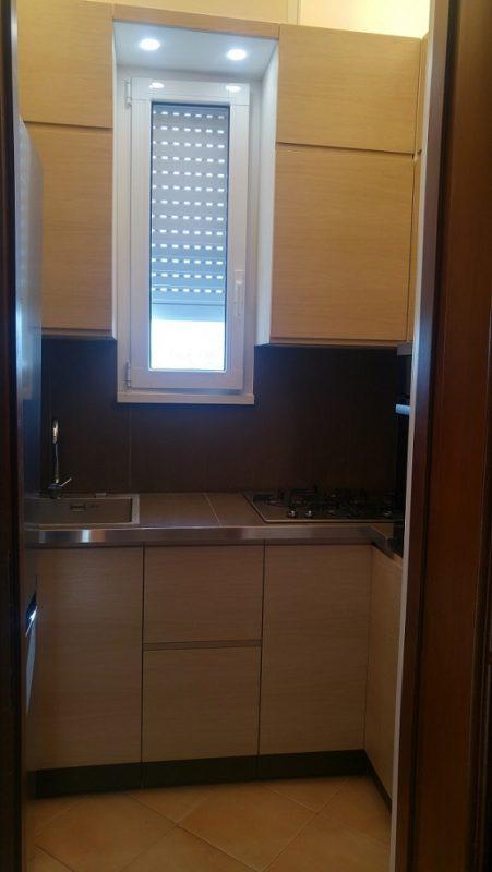 Piccola cucina rettangolare con finestra centrale in rovere spazzolato